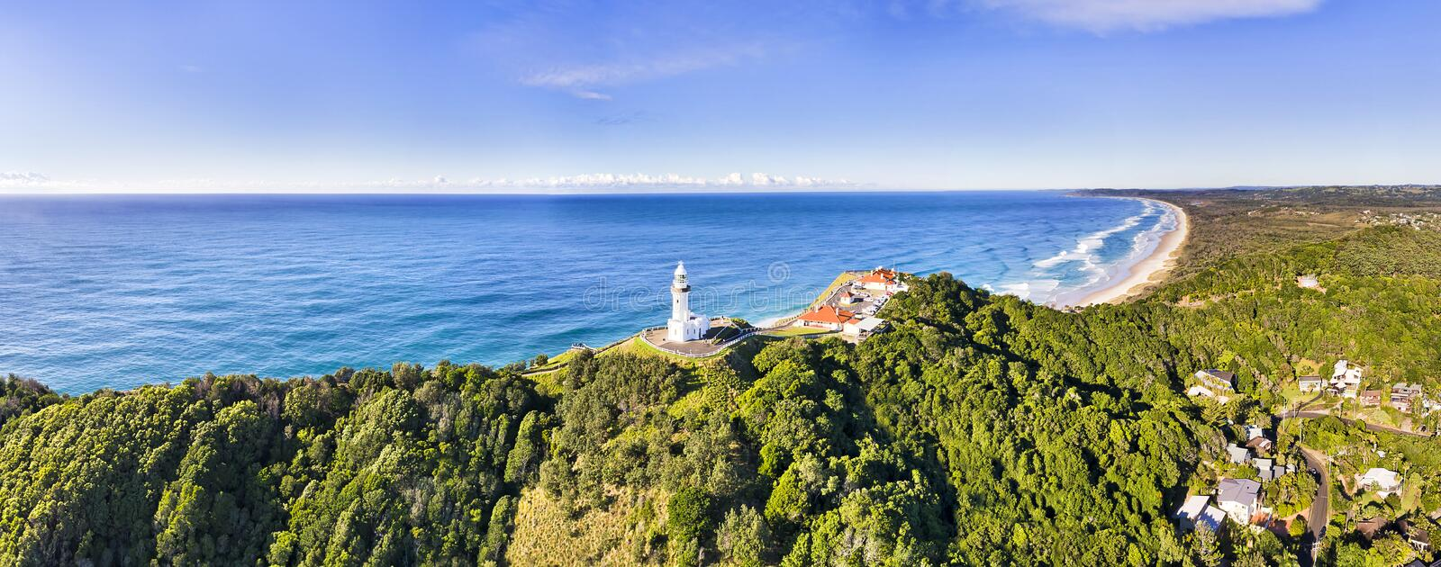 D Byron Bay LIghthouse short top pan. Sandstone headland hill range at the tip near Byron Bay town with wHite stone Byron Bay lighthouse on the top in wide stock photography