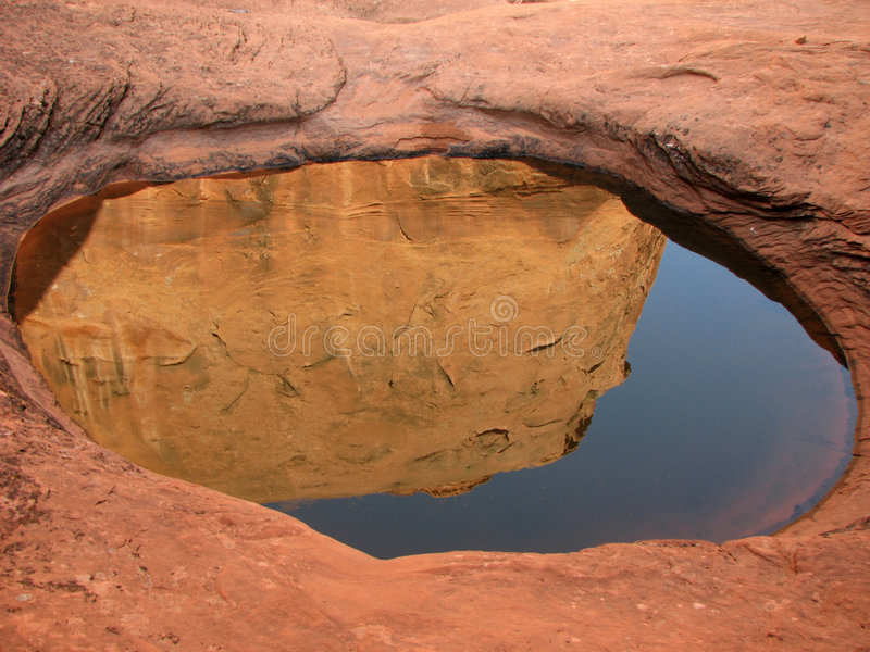 Sandstone pool reflection. Orange sandstone cliff and sky reflected in rock pool in Davis Gulch, Glen Canyon National Recreation Area, Utah stock image
