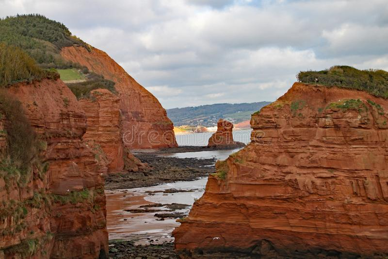 A sandstone sea stack at Ladram Bay near Sidmouth, Devon. Part of the south west coastal path. Sidmouth is visible in the. Background stock image