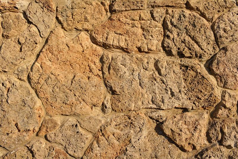 Sandstone wall made of irregular porous pieces of stone lit by the evening sun. Sandstone wall made of irregular pieces of stone lit by the evening sun royalty free stock images