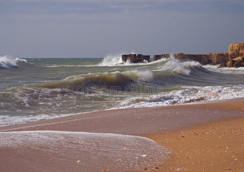 Sandstrand för grovt hav med härliga sandstenklippor arkivfoton