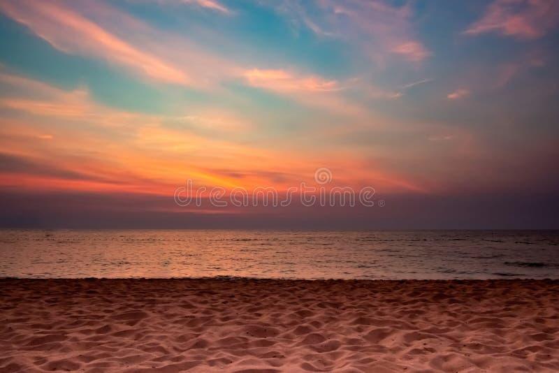 Sandstrandmeer auf Dämmerungshimmel-Wolkenhintergrund, Sonnensatzzeit stockfoto