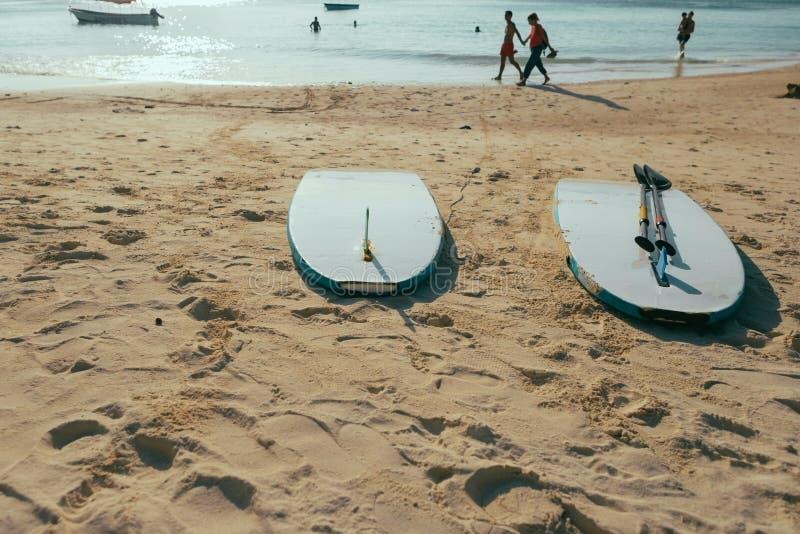 Sandstrandsonnenuntergangdämmerung Sommerhintergrund mit zwei Surfbrettern lizenzfreie stockbilder