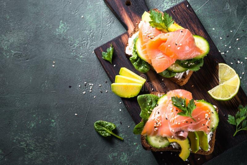 Sanduíche aberto com espinafres e o abacate salmon fotografia de stock royalty free