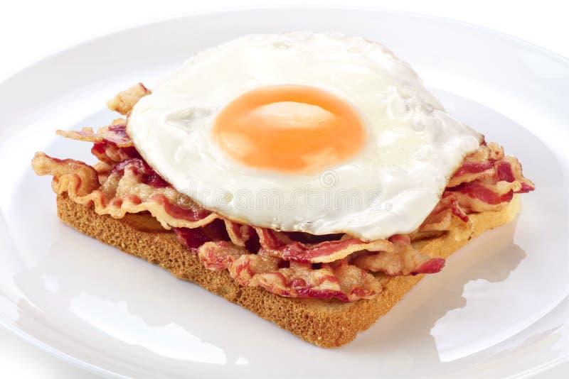 Sanduíche com bacon e ovo frito em uma placa imagens de stock royalty free