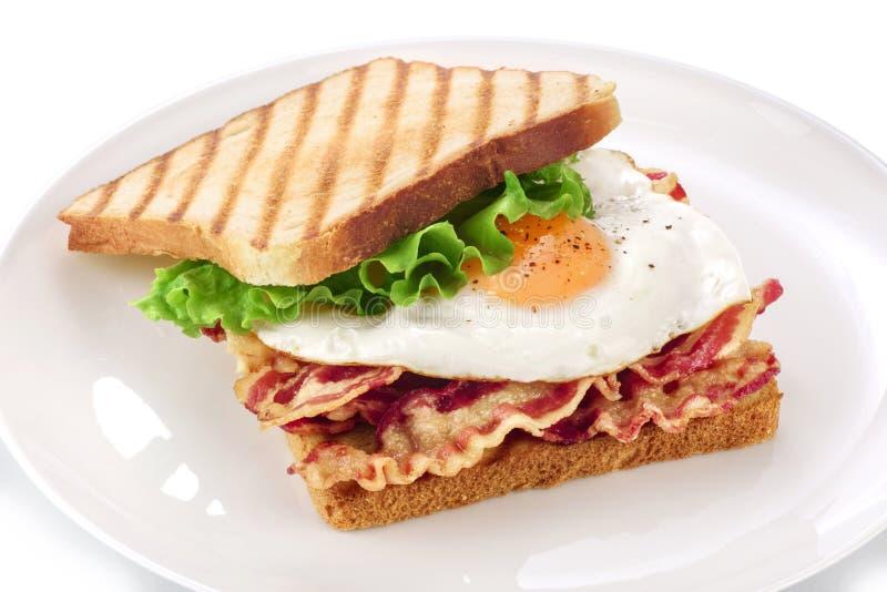 Sanduíche com bacon, ovo frito e alface em uma placa imagem de stock