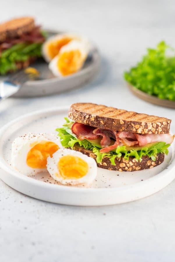 Sanduíche com bacon, pão preto, salada na placa fotografia de stock royalty free