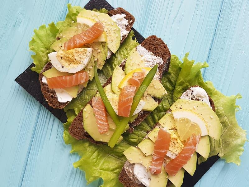 Sanduíche com do limão vermelho do almoço dos peixes do abacate o aperitivo de madeira azul gourmet rústico imagem de stock