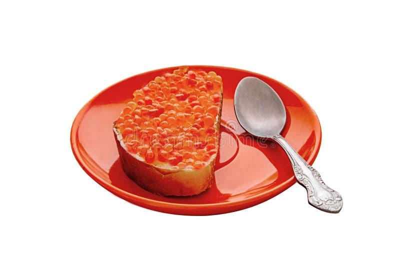 Sanduíche com o caviar vermelho na placa vermelha, colher, fundo branco fotos de stock royalty free