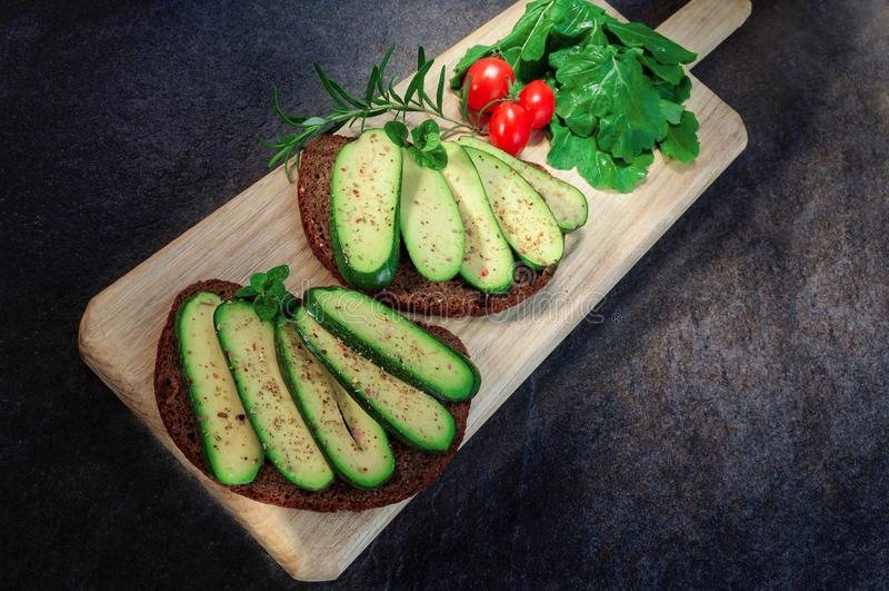 Sanduíche com o tomate sem sementes do abacate, do ovo e de cereja na placa de corte Abacate sem alguma semente Abacate do cockta foto de stock