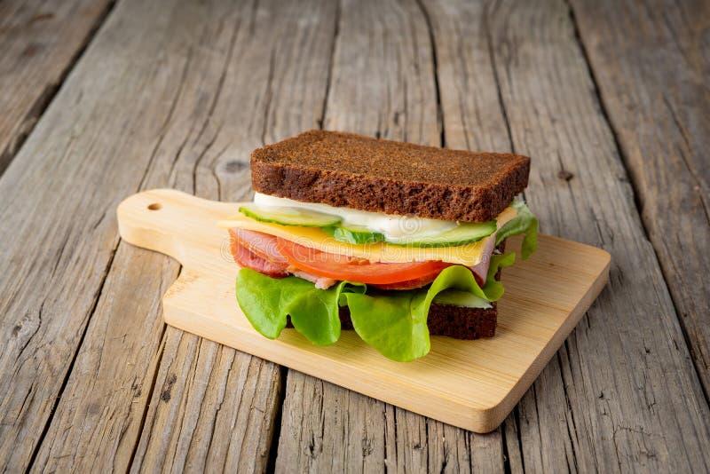 sanduíche com pão de centeio preto, presunto, queijo, tomates, pepinos imagens de stock