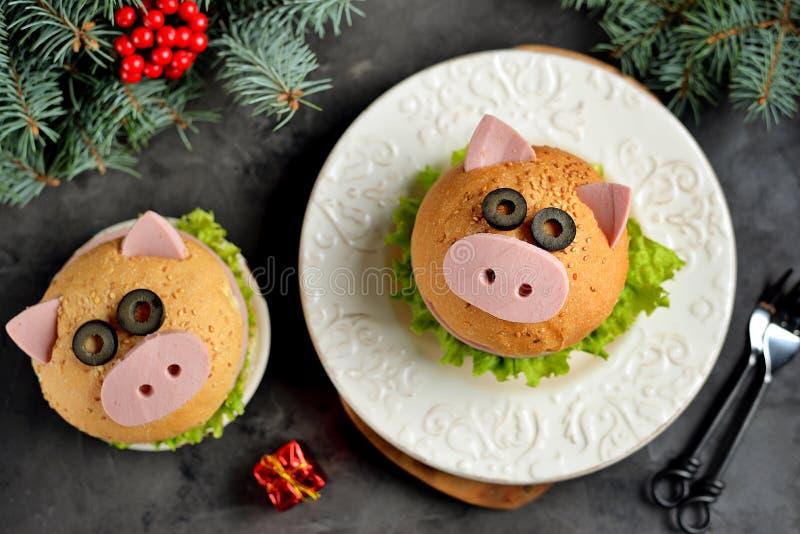 Sanduíche com presunto, queijo e alface sob a forma do porco bonito - símbolo de 2019 Fundo do Natal do café da manhã das criança foto de stock