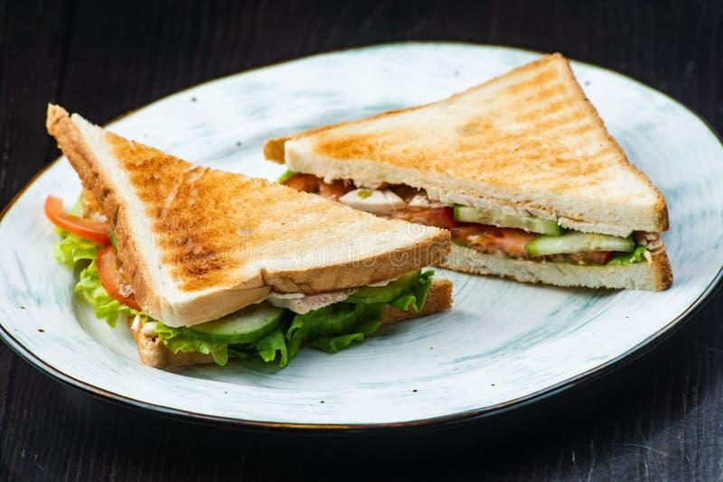Sanduíche com presunto, queijo, tomates, alface, e pão brindado Acima da vista no fundo escuro fotos de stock royalty free