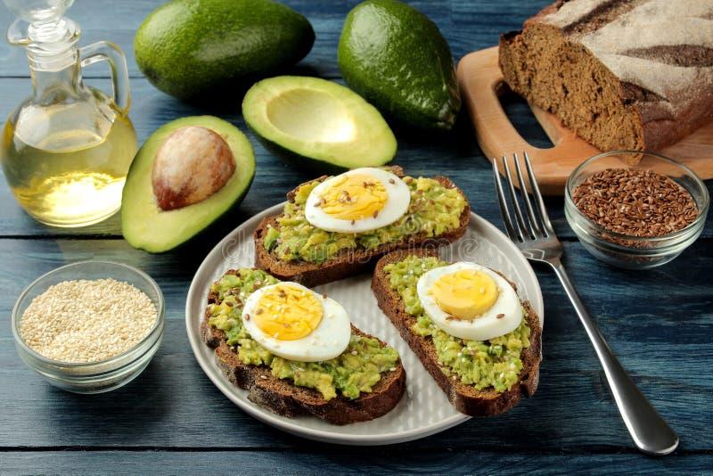 Sanduíche com puré e ovo do abacate em uma placa e em ingredientes para cozinhar em uma tabela de madeira azul imagens de stock