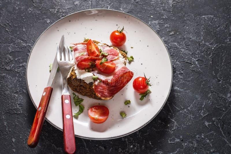 Sanduíche com tomates de cereja e prosciutto na placa sobre o fundo de pedra escuro fotos de stock royalty free