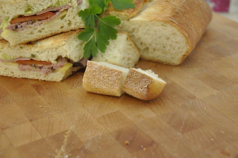 Sanduíche da carne assada na placa de desbastamento de madeira foto de stock