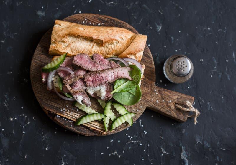 Sanduíche de bife em uma placa de madeira fotografia de stock