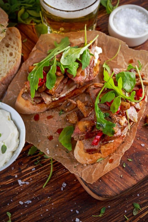 Sanduíche de bife grelhado com cogumelos, manteiga do queijo do ` s da cabra e folhas do rucola na parte superior Cerveja do ouro fotografia de stock royalty free