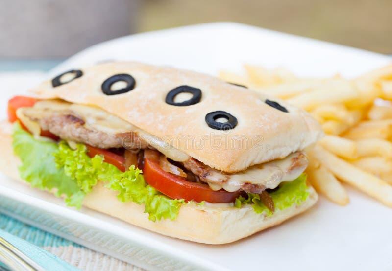 Sanduíche de Ciabatta com carne, os tomates, queijo e alface grelhados com fundo do verão das batatas fritas imagens de stock royalty free