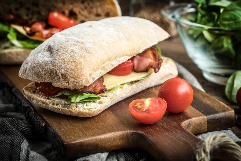 Sanduíche de Ciabatta com rúcula salada, bacon e queijo amarelo fotografia de stock royalty free
