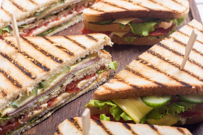 Sanduíche de clube com tomates, pepino, presunto e queijo imagem de stock royalty free