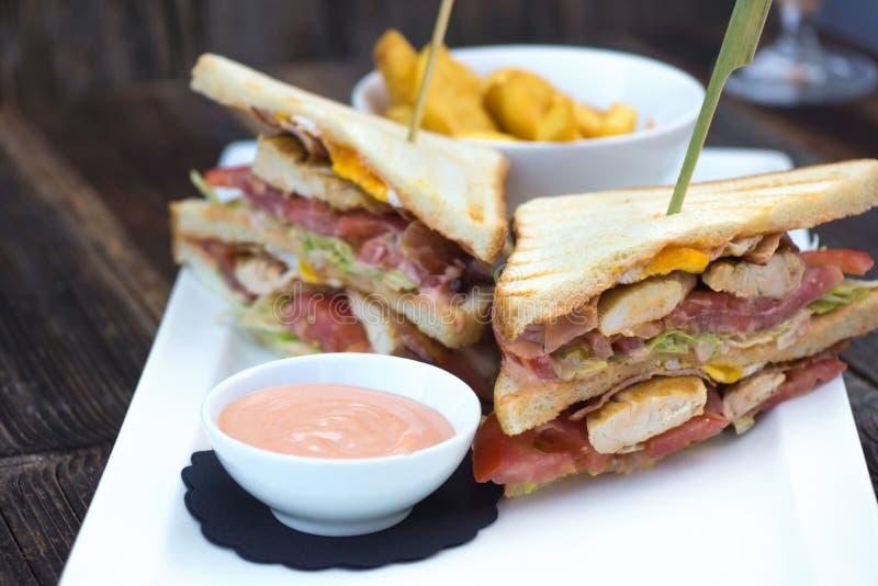 Sanduíche de clube no brindado, servido com batatas fritas douradas friáveis da batata fotografia de stock