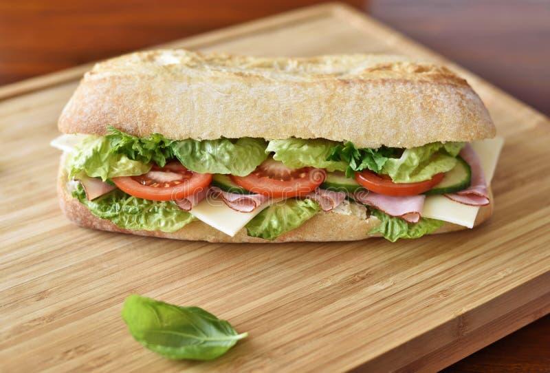 Sanduíche delicioso do ciabatta com presunto, tomates, salada fresca e pepino foto de stock