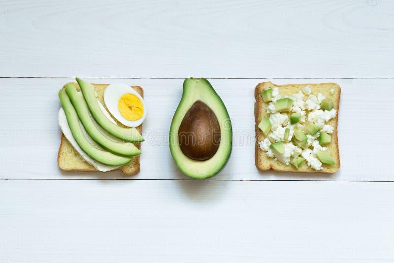 Sanduíche do abacate com o ovo isolado Brinde no fundo de madeira branco, vista superior do abacate e do ovo imagens de stock royalty free