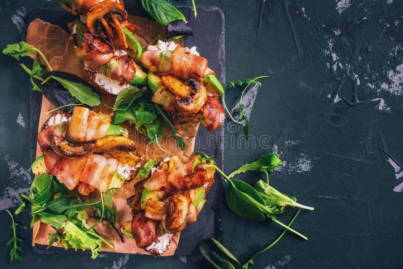 Sanduíche do abacate com o pão caseiro do ciabatta, cozinhado com o abacate cortado fresco e bacon e cogumelos friáveis fritados  fotografia de stock