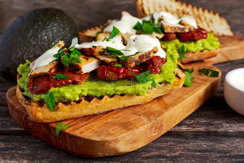 Sanduíche do abacate com os tomates secados luz do sol, carne de porco roasted e ervas do molho fotografia de stock royalty free