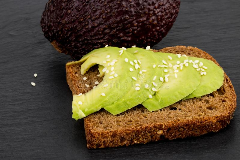 Sanduíche do abacate no pão de centeio escuro feito com avocad cortado fresco fotografia de stock royalty free