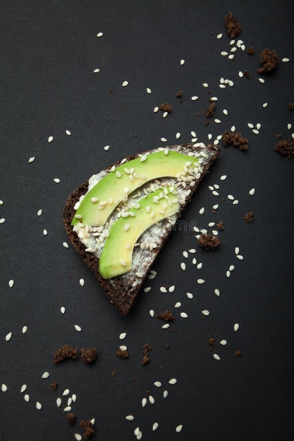 Sanduíche do abacate, do queijo, do pão preto e das sementes de sésamo em um fundo preto, verticalmente fotos de stock