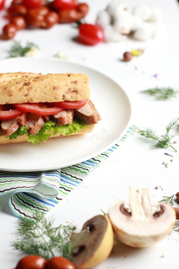 Sanduíche do alimento com carne e vegetais na tabela branca foto de stock royalty free