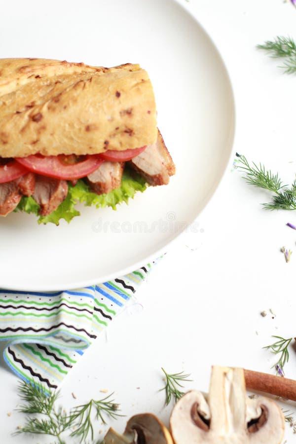 Sanduíche do alimento com carne e vegetais na tabela branca imagem de stock royalty free