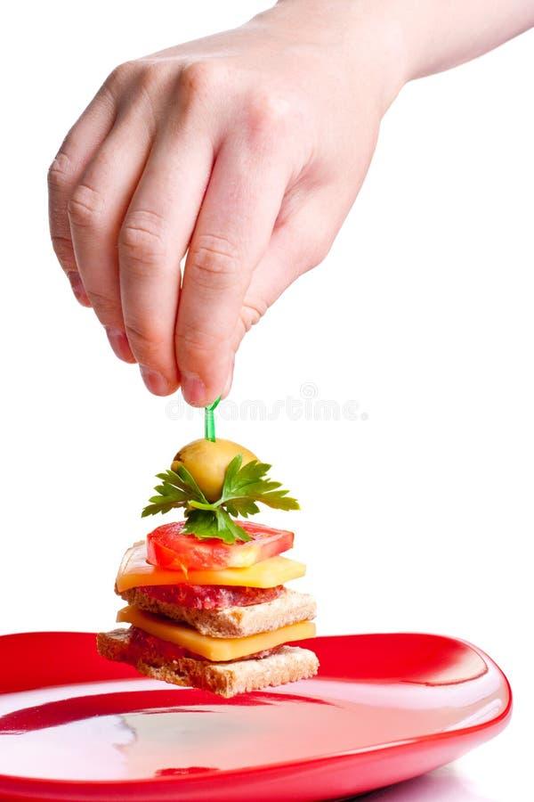 Sanduíche do aperitivo da colheita da mão da placa vermelha imagem de stock