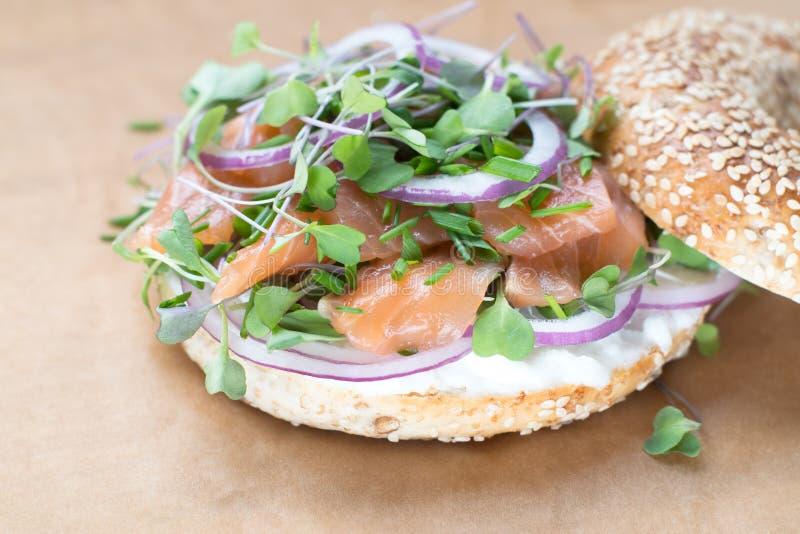 Sanduíche do Bagel com queijo do creame, salmão, cebola, tomate, verdes, ch fotografia de stock