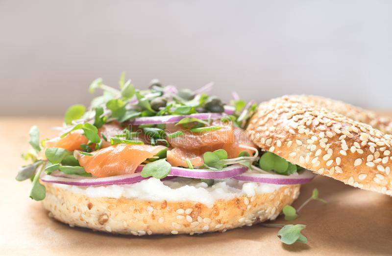 Sanduíche do Bagel com queijo do creame, salmão, cebola, tomate, verdes, ch foto de stock