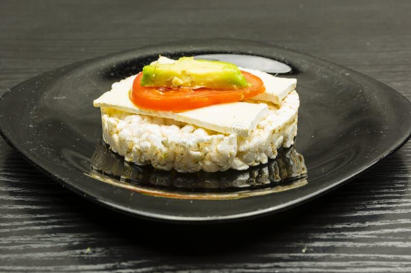 Sanduíche do bolo de arroz com queijo, tomate e abacate imagens de stock royalty free