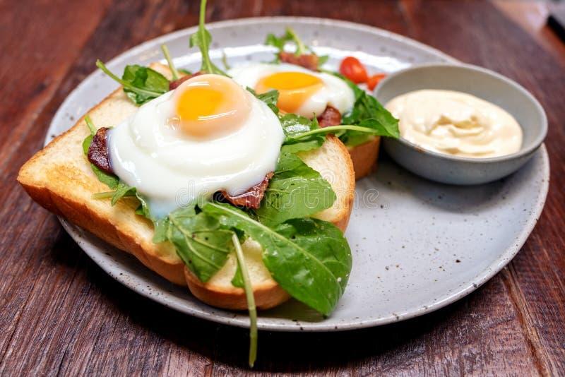 Sanduíche do café da manhã com ovos, bacon e creme de leite em uma placa fotografia de stock