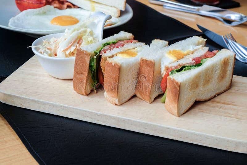 Sanduíche do café da manhã inglês com ovos fritos, salsichas, bacon, galinha, brindes na manhã fotografia de stock