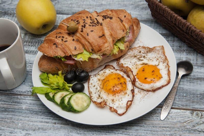 Sanduíche do croissant com Fried Eggs, pepinos e azeitonas, frutos e legumes frescos e xícara de café na placa branca sobre r cin fotos de stock