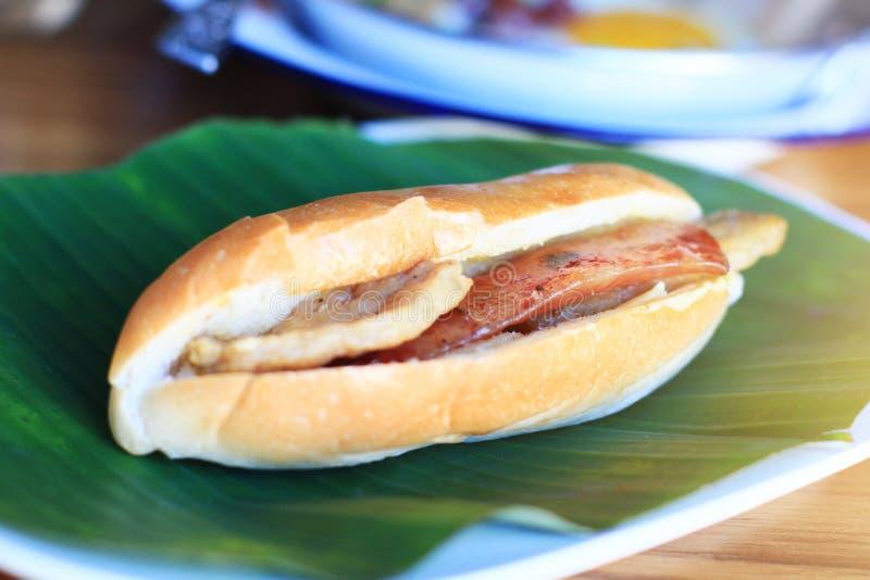 Sanduíche do pão do Baguette com queijo, presunto na folha verde fresca da banana na tabela de madeira em caseiro fotografia de stock