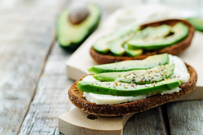 Sanduíche do pão de centeio com queijo do abacate e de cabra imagens de stock