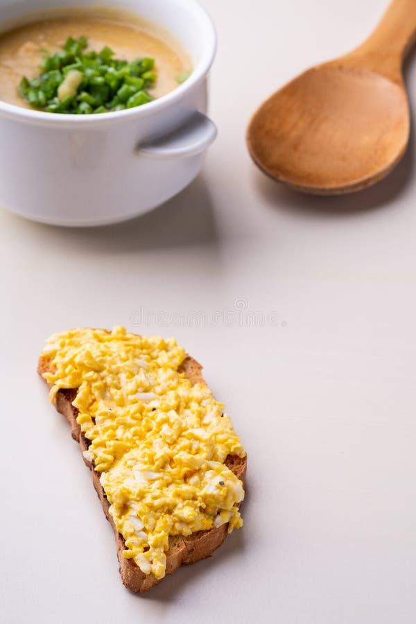 Sanduíche do queijo e puré da sopa com a cebola na placa branca com espátula de madeira foto de stock royalty free