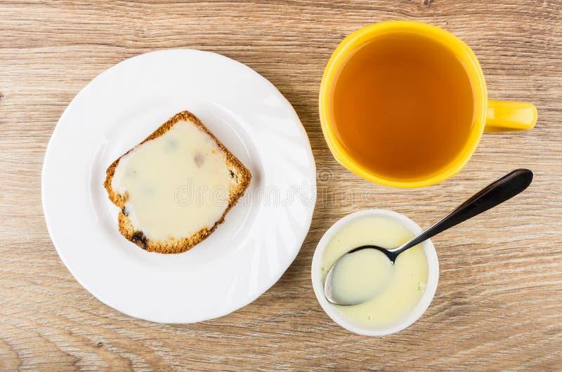 Sanduíche do queque com leite condensado na placa, chá fotografia de stock royalty free