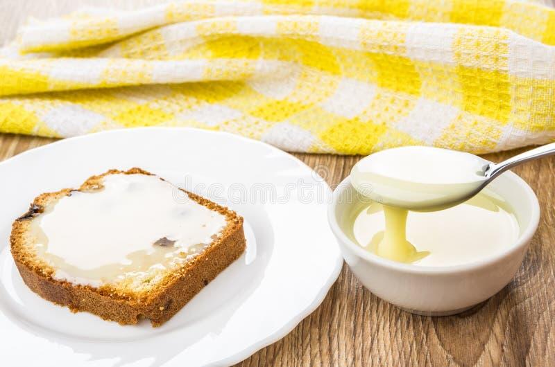 Sanduíche do queque e da colher com leite condensado acima da bacia fotos de stock