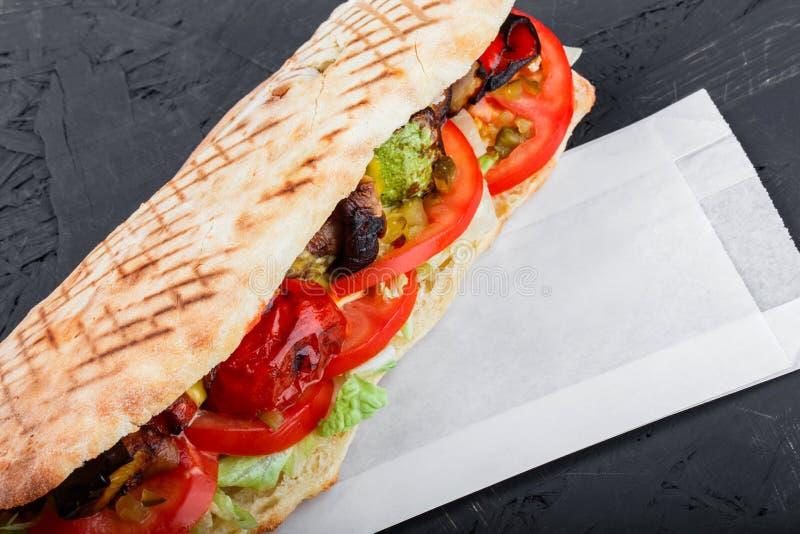 Sanduíche do vegetariano dos vegetais grelhados e do pão fresco do pão árabe no fundo de madeira escuro fotografia de stock