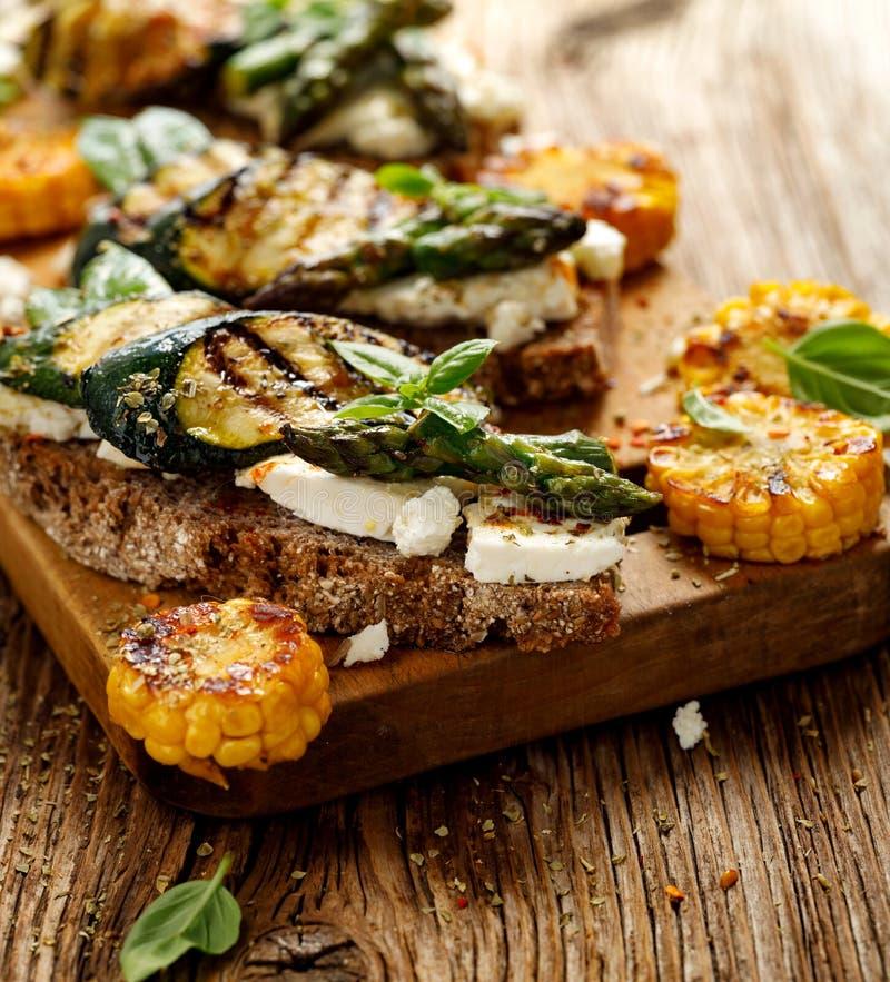 Sanduíche do vegetariano Sanduíches do pão de Wholemeal com queijo de feta, o abobrinha grelhado, aspargo verde, ervilhas de açúc foto de stock