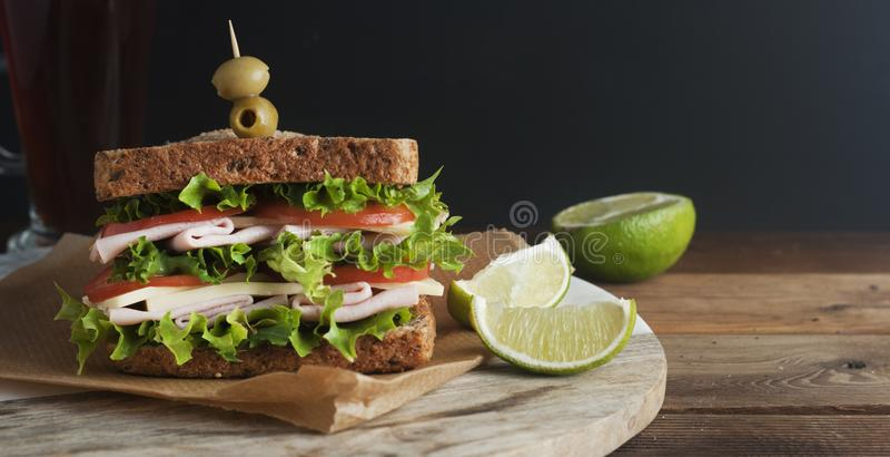 Sanduíche dobro com presunto, queijo, alface, tomate e azeitonas verdes Pão inteiro da grão O petisco ou leva embora o alimento F foto de stock royalty free