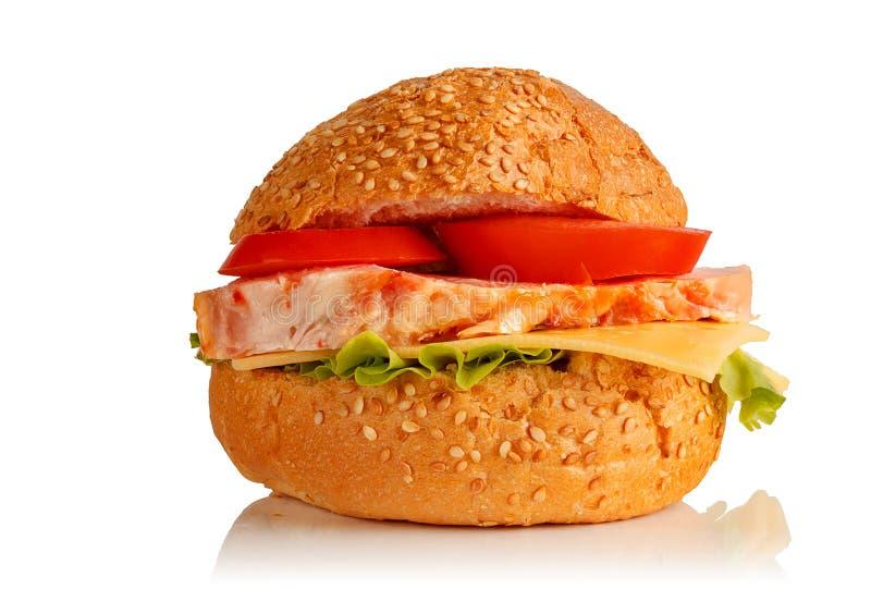 Sanduíche dos bolos com sementes de sésamo, carne, salada, tomates e imagens de stock